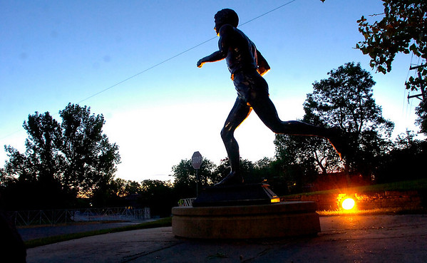 The statue of Olympic and former Bolder Boulder champion Frank Shorter stands in the pre-dawn darkness near the finish line of the Bolder Boulder on Monday May 31, 2010<br /> Photo by Paul Aiken / The Camera / May 31, 2010