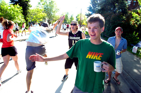 From left to right, Brian Sellers, Mike Sellers and Andrew Van Diepenbrugge, high five runners during the Bolder Boulder on Monday May 31, 2010<br /> Photo by Paul Aiken / The Camera / May 31, 2010