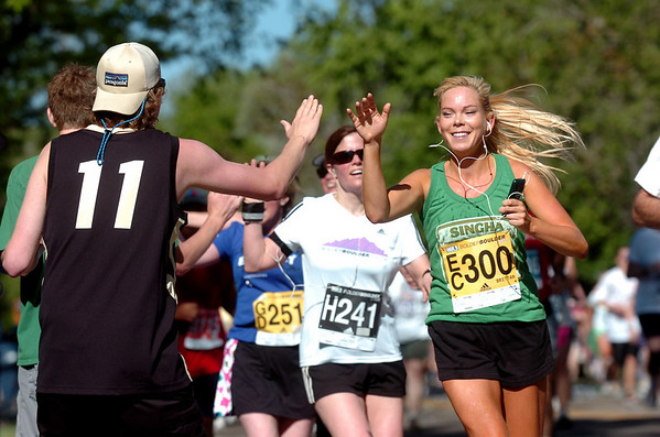 Brian Sellers gets a high five from runner Brittan Maassen of Boulder during the Bolder Boulder on Monday May 31, 2010<br /> Photo by Paul Aiken / The Camera / May 31, 2010