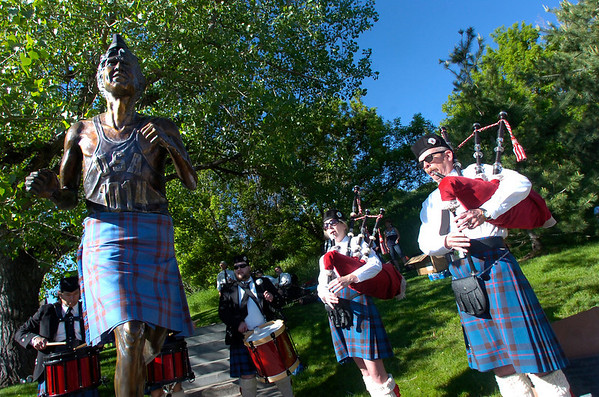 Scott Plummer, left and Laura Boothby of the Centennial State Pipes and Drums play near the statue of Frank Shorter wearing a kilt near the finish line of the Bolder Boulder on Monday May 31, 2010<br /> Photo by Paul Aiken / The Camera / May 31, 2010
