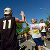 Brian Sellers gets a high five from runner Elizabeth Peters of Denver during the Bolder Boulder on Monday May 31, 2010<br /> Photo by Paul Aiken / The Camera / May 31, 2010