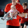 BOLDER<br /> Doug Vincent of Erie crosses the finish line with daughter Grace, 11 months, after taking her from his wife's arms in the stadium during the 32nd Annual Day Bolder Boulder on Monday.<br /> Photo by Marty Caivano/Camera/May 31, 2010