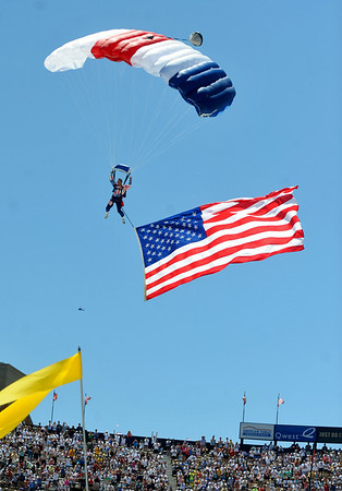 BOLDER<br /> A parachute jumper brings the American flag into Folsom Field during the Memorial Day tribute held during the 32nd Annual Day Bolder Boulder on Monday.<br /> Photo by Marty Caivano/Camera/May 31, 2010