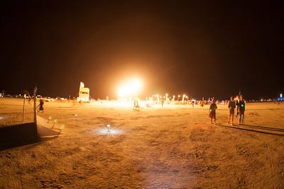 Random fire lighting up the playa at night.