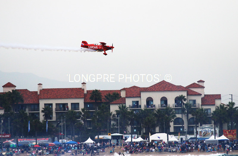 LUCA OIL bi-plane over beach and hotel.