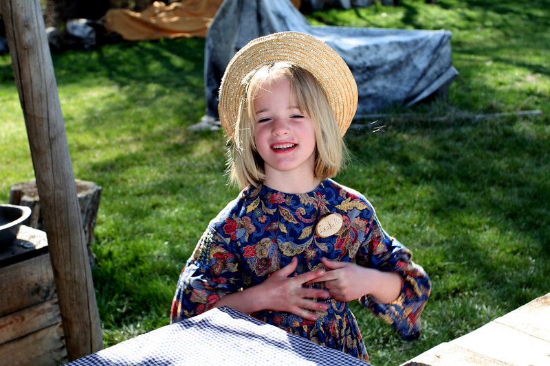 A young volunteer smiles for the camera while helping out at the Pioneer Settlement.