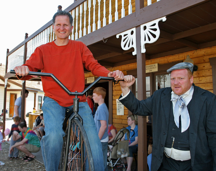 Bryce made this old bike himself. Here, he helps a visitor enjoy sitting on it.