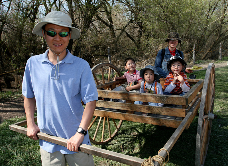 A beautiful family takes a spin on a handcart.