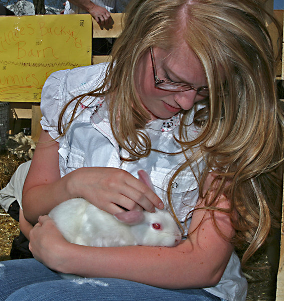 A young woman enjoys the quiet closeness of a young bunny. A moment like this seems to make time stand still.