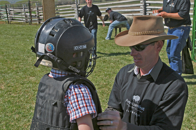 A volunteer from USU's Parks and Recreation Program helps a young participant get ready for the Li'l Buckaroo Rodeo.