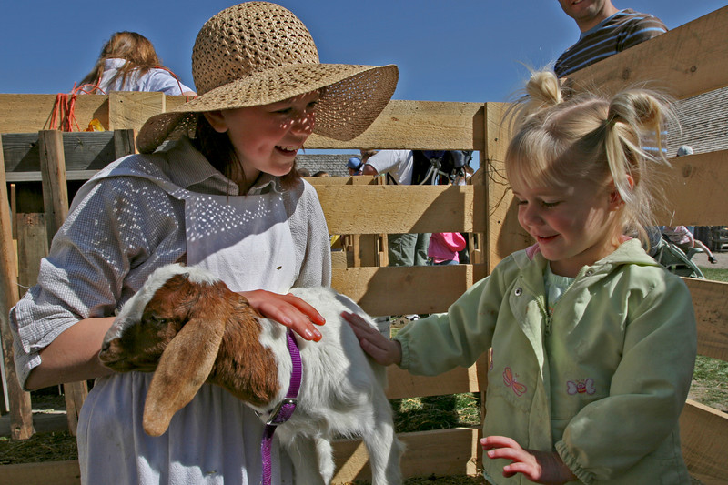 A volunteer and a young girl enjoy interacting with a young goat together.