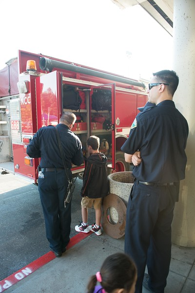 Firefighter showing one of the kids the apparatus.