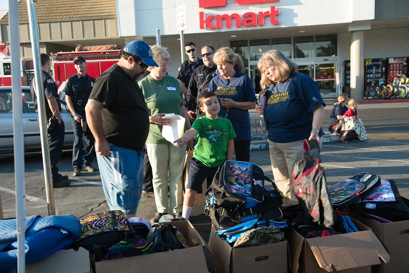 Gold Country Kiwanis members Janice' Moule and Karen Poskus help one of the kids pick out a back pack with school supplies after being taken shopping by a volunteer.<br /> At the beginning of each school year, Gold Country Kiwanis buys each child signed up for the program approximately $125 of new school clothing and gives away a backpack with school supplies.<br /> K-mart and Gold Country Kiwanis partner in this event.<br /> Thanks to Grass Valley Fire Dept. for coming out and showing support. The kids loved it.