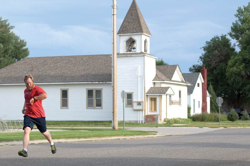Matthew Gaston | The Sheridan Press<br>Brett Garden checks his watch as hits the home stretch of the Tongue River Community Center's Back-to-School 5K Thursday, Aug. 8, 2019.