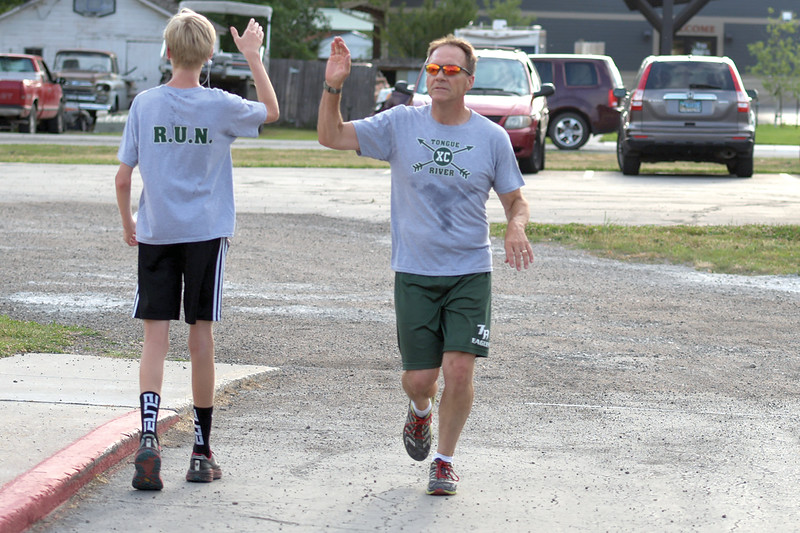 Matthew Gaston | The Sheridan Press<br>Isaiah Coty, left, high fives Tongue River High School cross country coach Tim Maze as he finishes the Back-to-School 5K hosted by the Tongue River Valley Community Center in Ranchester Thursday, Aug. 8, 2019.