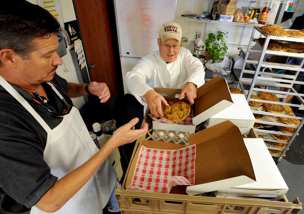 . Ted Ruckstahl, left, and Joe Dunigan, box up peach pies  on Thursday. Julie Dunigan, owner of Jules Gourmet Catering, and her staff, are making 500 pies and 4,500 servings of peach cobbler for the Lafayette Peach Festival this weekend. For more photos and a video of the pie baking, go to www.dailycamera.com Cliff Grassmick  / August 15, 2013