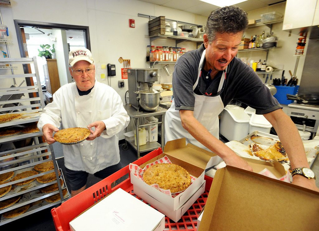 . Ted Ruckstahl, right, and Joe Dunigan, box up peach pies  on Thursday. Julies Dunigan, owner of Jules Gourmet Catering, and her staff, are making 500 pies and 4,500 servings of peach cobbler for the Lafayette Peach Festival this weekend. For more photos and a video of the pie baking, go to www.dailycamera.com Cliff Grassmick  / August 15, 2013