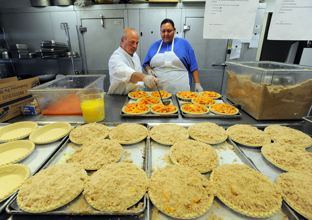 . Scoot Riemer, left, and Violeta Aguayo, make peach pies on Thursday. Julie Dunigan, owner of Jules Gourmet Catering, and her staff, are making 500 pies and 4,500 servings of peach cobbler for the Lafayette Peach Festival this weekend. For more photos and a video of the pie baking, go to www.dailycamera.com Cliff Grassmick  / August 15, 2013