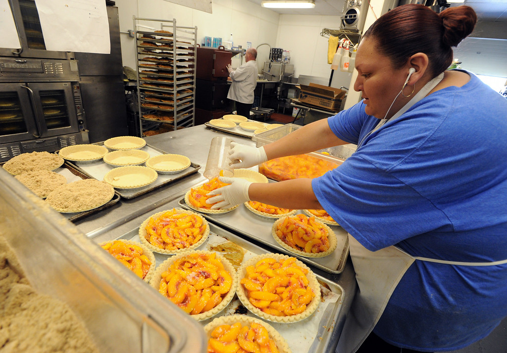 . Violeta Aguayo  puts peaches in the pie crusts for baking on Thursday. Julie Dunigan, owner of Jules Gourmet Catering, and her staff, are making 500 pies and 4,500 servings of peach cobbler for the Lafayette Peach Festival this weekend. For more photos and a video of the pie baking, go to www.dailycamera.com Cliff Grassmick  / August 15, 2013