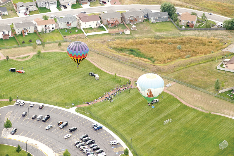 Matthew Gaston | The Sheridan Press<br>Students from Woodland Park Elementary School gather in the field next to the school to witness the launch of three hot air balloons Friday, Sept. 6, 2019.