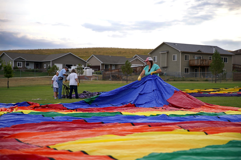 Matthew Gaston | The Sheridan Press<br>Reagan O'Neal helps to spread out Bob Kross' hot air balloon in the field adjecent to Woodland Park Elementary School Friday, Sept. 6, 2019.