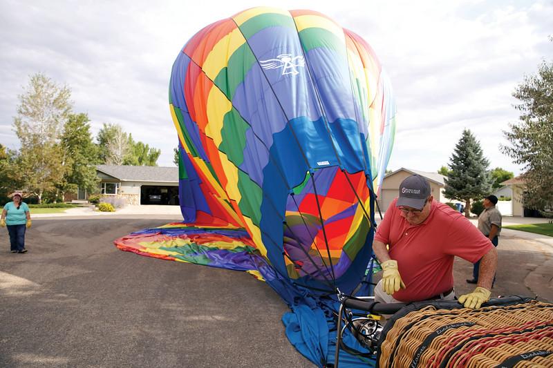 Matthew Gaston | The Sheridan Press<br>Hot air balloon pilot Bob Kross climbs out of the basket after a smooth landing near Sagebrush Elementary School to begin the process of breaking down the balloon Friday, Sept. 6, 2019.