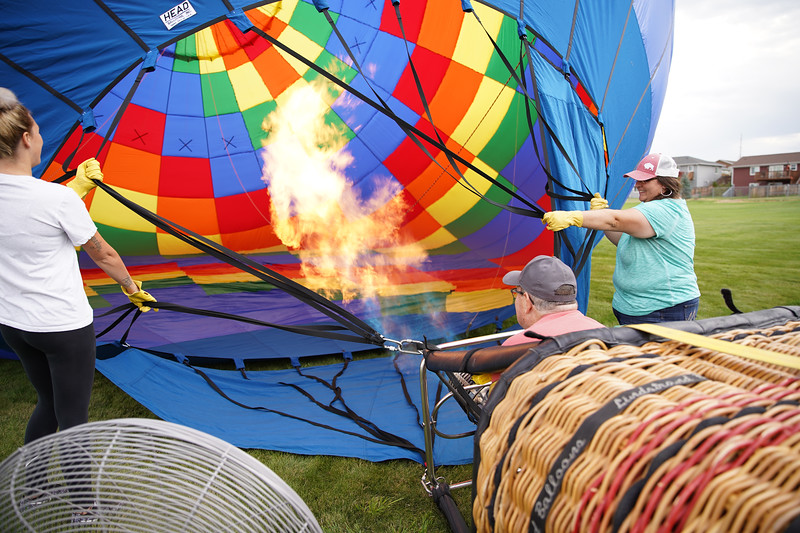Matthew Gaston | The Sheridan Press<br>Jamie Bougie, left, and Reagan O'neil, right, hold the balloon open while pilot Bob Kross fires the burner in order raise the balloon Friday, Sept. 6, 2019.