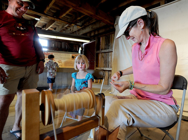 "Angella Dirks, right, shows Anni Haakenson, 5, and her dad, Dean how to spin yard.<br /> Boulder County  hosted  Barnyard Critter Day  on June 24 at the Agricultural Heritage Center in Longmont, at 8348 Highway 66.<br /> For more photos and a video of the event, go to  <a href=""http://www.dailycamera.com"">http://www.dailycamera.com</a>.<br /> Cliff Grassmick / June 24, 2012"
