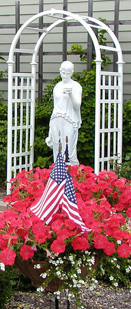 Photos by Debbie Blank | The Herald-Tribune<br /> PATRIOTIC INSIDE AND OUT: The Batesville Area Historical Society Museum offers a military display inside the building and landscaping with flags outside.