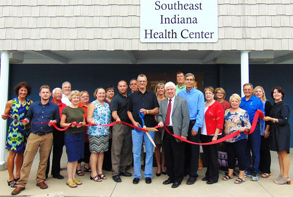 Debbie Blank | The Herald-Tribune<br /> The ribbon officially opening the Southeast Indiana Health Center housed within the Batesville Area Resource Center was cut by donor Ron Fledderman. Helping him are (front row from left) Batesville Area Chamber of Commerce office coordinator Patricia Hatcher,  community development director Steven Harmeyer, food pantry co-coordinator Anne Baran, BARC President Angela Byers, SEIHC manager Paul Tyrer, Mayor Mike Bettice, SEIHC board members Dr. Steve Glaser and Connie DeBurger, BACC Vice President Bev Broughton, BARC board member Dennis Harmeyer and city administrative assistant Andrea Wade; (back row) BARC board members Bob Erne, Robert Jester and Lisa Haessig, BARC past President and board member Sue Siefert, BARC board member Ed Krause, economic development director Sarah Lamping, SEIHC board member Brad Mehlon, BARC Vice President Dr. Jere Schoettmer and BACC President Carrie Rupp. Donor Doug Bessler is not pictured.