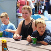 Diane Raver | The Herald-Tribune<br /> Ben Parker (from right), 10, Cincinnati; Alisha Eadens, Osgood; and Jackson Eadens, 5, Osgood; took some time to cool down at the Aug. 5 fest.