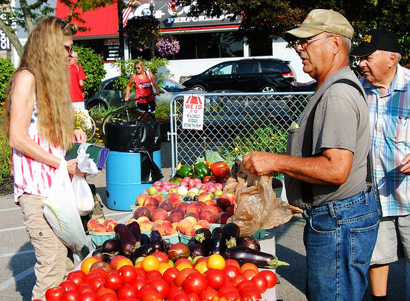 Debbie Blank | The Herald-Tribune<br /> Peaches attracted Debbie Ybarra (from left), Greensburg, to the stand operated by Richard Salatin and Gabe Seidman, Moores Hill.