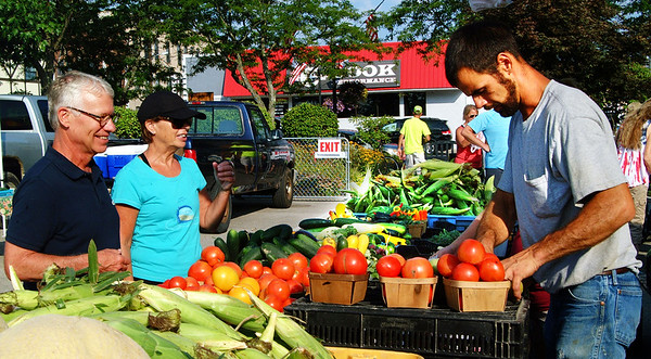 Debbie Blank | The Herald-Tribune Doug and Jane Weigel (from left), Oldenburg, scope out the tomatoes sold by Lucas and Christy (not pictured) Ludwig, Batesville. She also serves as market master.