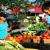 Debbie Blank | The Herald-Tribune<br /> Doug and Jane Weigel (from left), Oldenburg, scope out the tomatoes sold by Lucas and Christy (not pictured) Ludwig, Batesville. She also serves as market master.