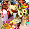 Debbie Blank | The Herald-Tribune<br /> Gina Grote, Batesville, and daughter Laura buy sunflowers from Sharon Steinfort, Batesville, at a stand that offers a fantastic variety.