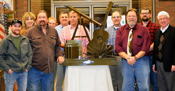 Photos courtesy of Lisa Barnett Chris Hoegeman (front row from left) and Bob Maple of Red Forge Weld, Morris, created an aluminum sculpture of Mike Kruse's favorite initiatives -- reading, astronomy and music. Library trustees (back row from left) Vice President Anne Amrhein, Nance Widdowson, Secretary Thomas Barnett, President Mark Stenger, Treasurer Peter Mack and Mark Masavage (Jeff Ollier was absent) presented the sculpture to the library in his honor. It will be installed outside the building this spring.
