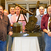 Photos courtesy of Lisa Barnett<br /> Chris Hoegeman (front row from left) and Bob Maple of Red Forge Weld, Morris, created an aluminum sculpture of Mike Kruse's favorite initiatives -- reading, astronomy and music. Library trustees (back row from left) Vice President Anne Amrhein, Nance Widdowson, Secretary Thomas Barnett, President Mark Stenger, Treasurer Peter Mack and Mark Masavage (Jeff Ollier was absent) presented the sculpture to the library in his honor. It will be installed outside the building this spring.