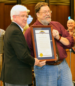 Mayor Mike Bettice (left) reads a proclamation about the library director's achievements. It will be published in The Herald-Tribune soon.