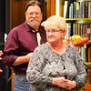Representing library employees, Karen Oesterling presents the retiree-to-be with a decorative wooden guitar created by Weberding Carving Shop. He received another present from BMPL Friends of the Library members. President Anne Baran gave Kruse a basket of fresh flowers interspersed with gift certificates.