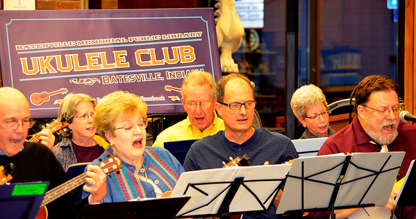 To kick off the public retirement party, Mike Kruse (far right in front row) leads BMPL Ukelele Club members (front row from left) Terry Geisen, Wauneta Fischmer, Ted Meyer; (back row) Renana Gross, Greg Lindemann and Janey Stephens and about seven others in playing and singing.