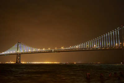 The Bay Bridge lights shining bright. I captured this photo in the rain. Notice the choppy waters. ref: 4e8cfd66-e90c-4a88-9264-0c518eb10476