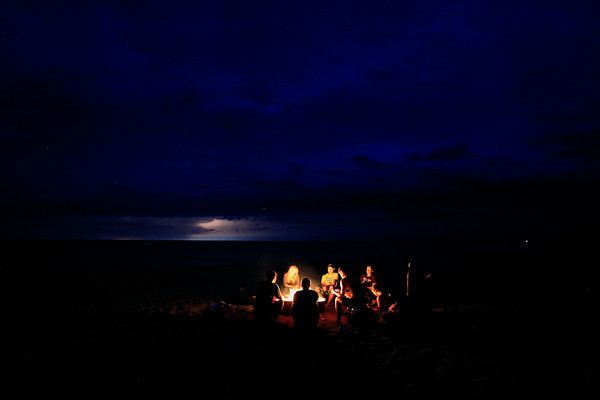 Record-Eagle/Jan-Michael Stump<br /> From left, Nate Schlehuber, Romaine Fields, Zach Lane, Eric Freeman, JohnPaul Morris, Julie Freeman and Alaina Stevens sit around a campfire at Empire Beach while lightning flashes on the horizon on Monday evening.