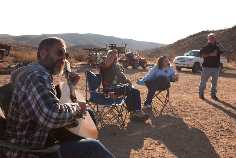 """Above Is Mark Algazy known around Bickel Camp as """"The Human Jukebox"""" because if you can name a song, he can play it and make it sound like the original recording. Mark is also a much renowned expert of Toyota carburetors and is currently vice president of  Friends of Last Chance Canyon.<br /> <br /> The Gift in the Rocks<br /> by Mark Algazy<br /> <br />  On a recent hike in the El Paso Mountains, I looked back down from my vantage point into the remnants of a long abandoned mining camp and thought to myself how solitary my old pickup truck looked there. However, as soon as I was done muttering aloud the words """"There's nobody here but me"""" a smaller voice inside me continued """"…and the energy of those who moved the rocks before you."""" Smiling, I returned to my truck, picked up a pen and paper and thought 'Alright then, tell me your story.' And so it is written.<br /> <br />  First there were the listeners. They were not born here, but followed the hum of the mountain to this place. Those who have felt the vibration that hovers near the subsonic need no further explanation. For them, it is enough to say that all who wander are not lost. They who listened moved rocks in search of food, temporary shelter, and in acknowledgement of their humbled connection to this place.<br /> <br />  Then came the dreamers. Drawn initially by worldly ends, their recorded failures were both predicted and preserved by a calculating world that knows nothing of the desert's secret treasures. Each passing year in the life of a prospector brought a reassessment of a life honed, not by magazine ads, but by the flow of the desert seasons. Without the panoply of distractions that portend a lifetime of unanswered questions, they picked up nuggets of circumspection at rates that would mystify our so called academics. The rocks they moved reflect the dreams they lost…and the dreams they found.<br /> <br />  Then came the diggers, and the builders of roads. They heard nothing but the hum of the machin"""
