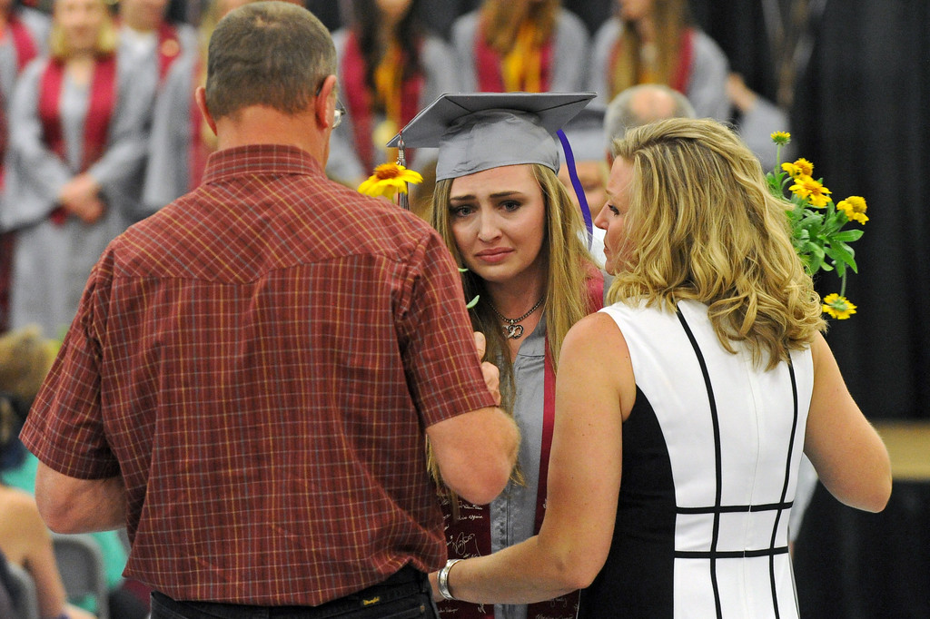 Madison Booth shares an embrace with her parents during the graduation ceremony on Sunday, May 28 at Big Horn High School. Mike Pruden | The Sheridan Press