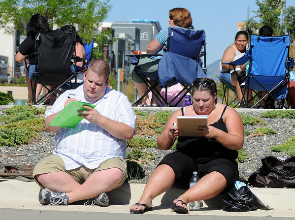 Mark Walker, left, of Ft. Collins sitting next to Katie Marino of Sacramento, California, fill out casting forms while waiting in line during Saturday's open casting call for The Biggest Loser 11 at Broomfield's 1st Bank Center.<br /> July 17, 2010<br /> Staff photo/ David R. Jennings