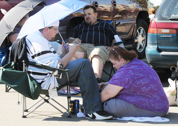 Matthew Thirsk, left, and his girl friend Jennifer Buen from Federal Heights, stay in the shade of their umbrella while waiting in line for Saturday's open casting call for The Biggest Loser 11 at Broomfield's 1st Bank Center.<br /> July 17, 2010<br /> Staff photo/ David R. Jennings