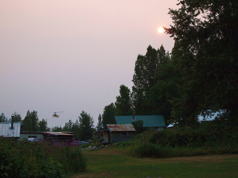 helicopter takes off under smokey sunset