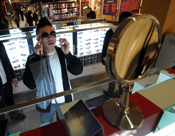 """Vuong Ly tries on sunglasses at New York Shades early Friday.<br /> Black Friday shoppers hit the stores by 5 a.m. at Flatiron Crossing in Broomfield.<br /> For a more photos of Black Friday, go to  <a href=""""http://www.dailycamera.com"""">http://www.dailycamera.com</a>.<br /> Cliff Grassmick / November 26, 2010"""