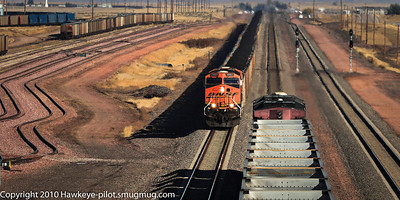 South-bound BNSF coal train meets North-bound empty UP about ten miles or so south of Bill, Wyoming. Facility to left of BNSF is for coal hopper repairs. This main line track is kept busy with over 100 trains per day.