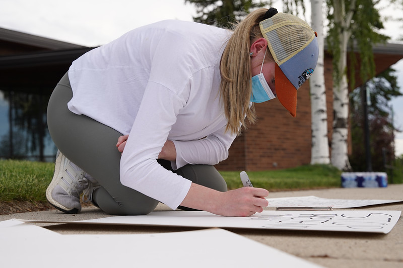 Matthew Gaston | The Sheridan Press<br>Bridgette Maxey makes signs for the Black Lives Matter Solidarity Protest on the sidewalk at the Sheridan Fulmer Public Library Friday, June 5, 2020.